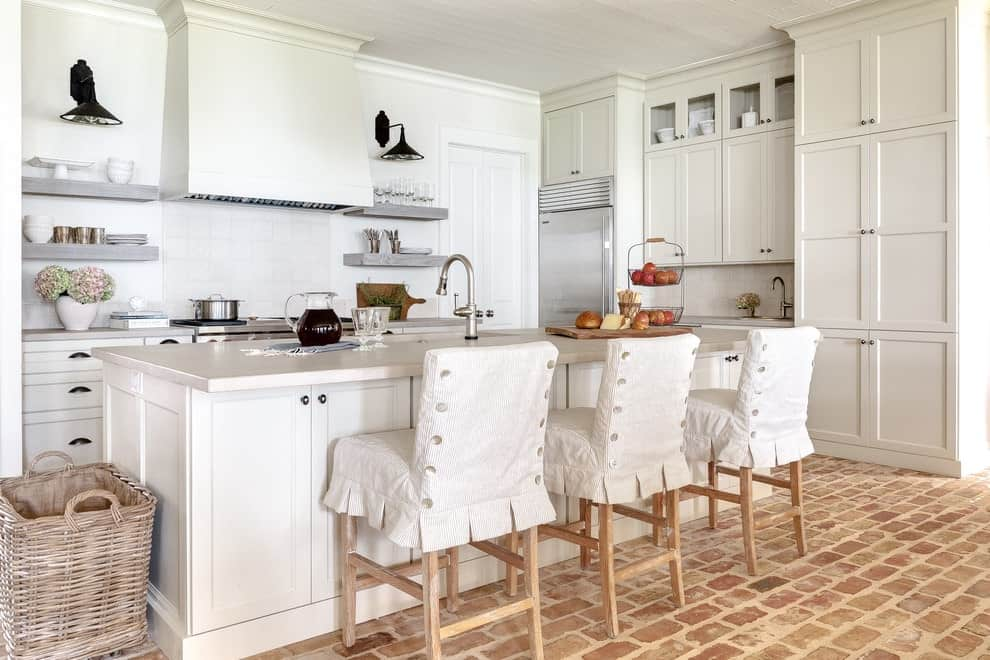 White cabinetry matches the breakfast island that's fitted with a sink and gooseneck faucet. It is lined with skirted counter chairs over brick flooring.