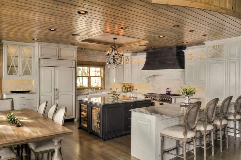 A black range hood complements the central island with marble countertop and built-in beverage fridges. It is illuminated by recessed lights and a fancy chandelier that hung from the tray ceiling clad in wood planks.