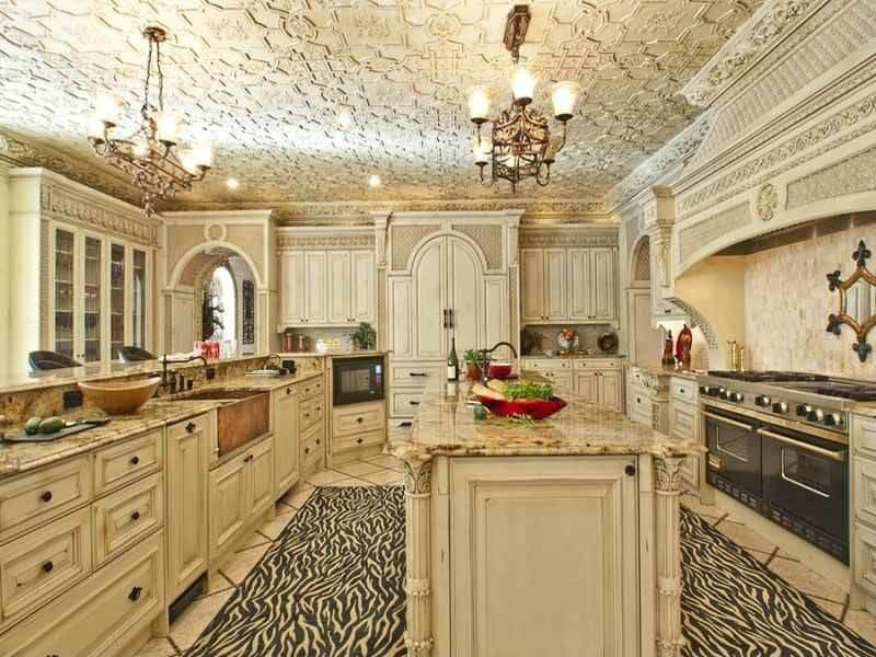 A pair of vintage chandeliers that hung from the ornate ceiling illuminates this kitchen showcasing black appliances and white cabinetry that matches the granite top island over a zebra rug.