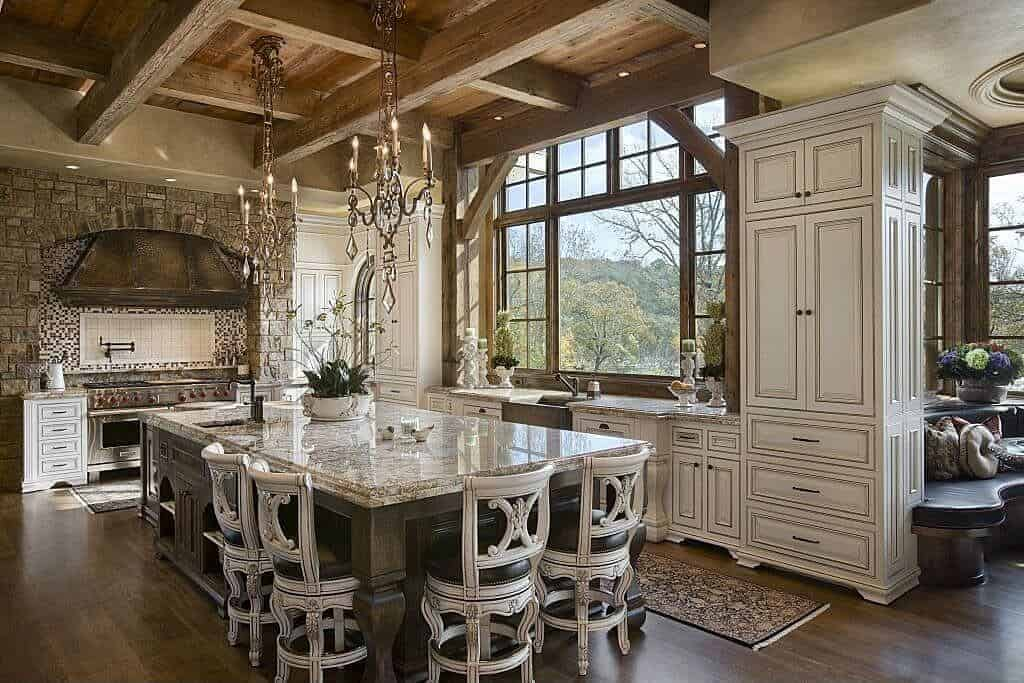 This kitchen features white cabinetry and a granite top island with distressed cushioned chairs lighted by fabulous candle chandeliers that hung from the wood beam ceiling. It has natural hardwood flooring and wooden framed windows overlooking a serene outdoor view.