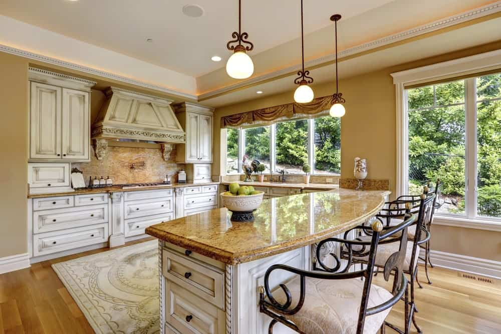 Cozy kitchen with smooth hardwood flooring and glass-paneled windows overlooking the outdoor greenery. It includes a printed area rug and a granite top breakfast bar lined with ornate cushioned stools.