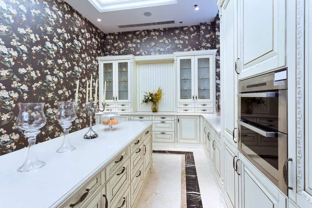 Clad in floral wallpaper, this kitchen offers a double wall oven and white cabinetry along with a matching breakfast bar that's topped with glassware and a chrome candle holder.