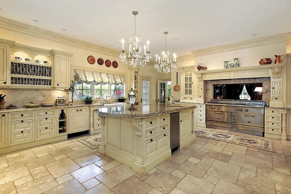 Shabby-chic style kitchen with limestone flooring and glazed windows dressed in a striped valance. It includes white cabinetry and a matching central island illuminated by fancy crystal chandeliers.