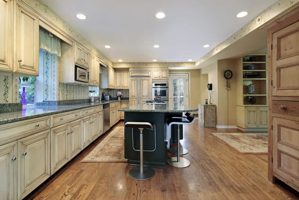 Modern bar stools sit at a black breakfast island topped with granite counter. This kitchen has recessed ceiling lights and shabby chic rugs that lay on the natural hardwood flooring.