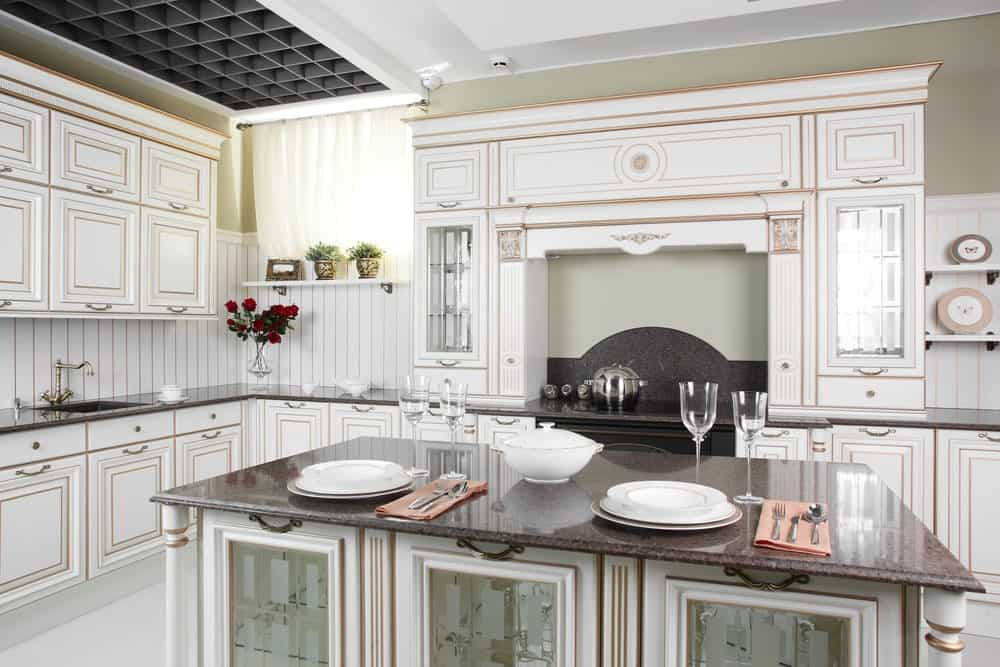 This kitchen boasts a granite top island bar with columns on the sides along with white cabinetry against the beadboard backsplash accented with gold trims.