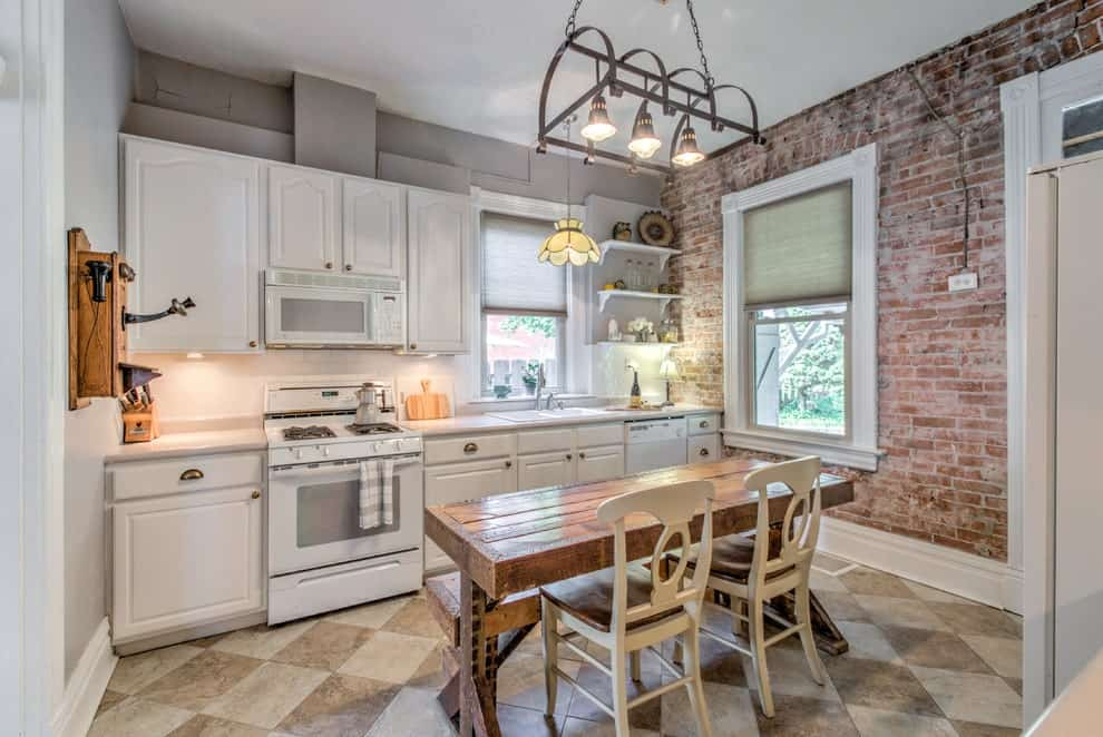 An eat-in kitchen with a wooden dining set and white appliances that blend in with the cabinets. It has a red brick accent wall and checkered tiled flooring arranged in a diamond pattern.