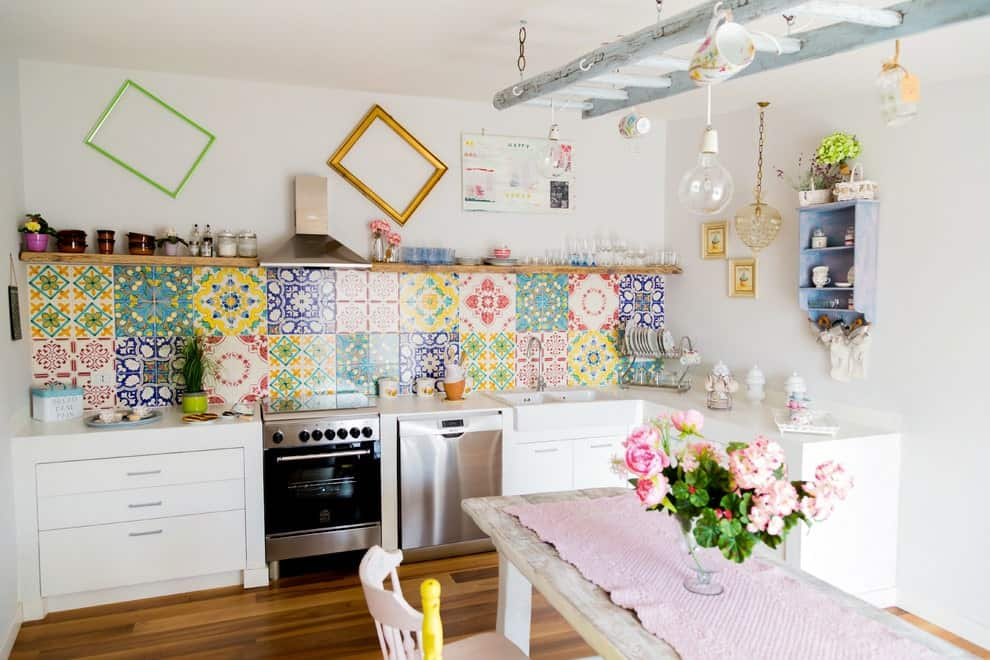 Colorful decorative backsplash tiles add a gorgeous accent in this kitchen that's designed with multi-colored frames and a distressed blue ladder that doubles as a rack.