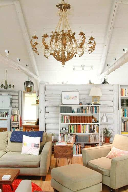 A large brass chandelier hangs over the beige sofa and lounge chair paired with a matching ottoman. There's a white shelving unit behind that's filled with books and decors.
