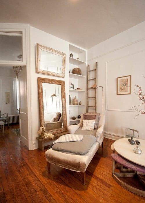 The shabby-chic style living room features a cozy lounge chair with wooden framed mirrors on the side fixed against the white walls. It includes built-in shelving and a ladder that doubles as a rack.