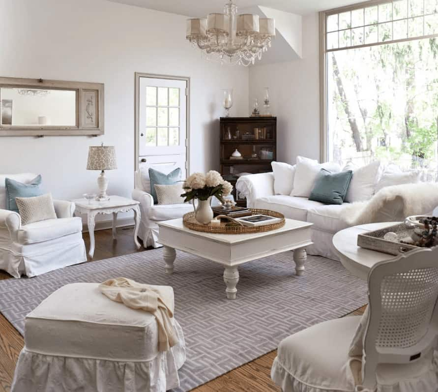 The bright living room features skirted seats and a white coffee table over a gray patterned rug. It is illuminated by a shade chandelier along with natural light from the full height window.