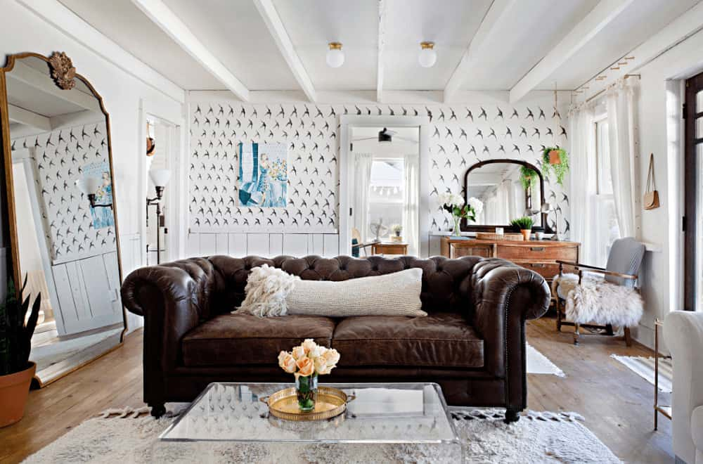 White living room clad in lower beadboard wall that's dominated by patterned wallpaper. It has a glass coffee table and a chesterfield sofa with a large mirror on the side creating a larger visual space in the room.