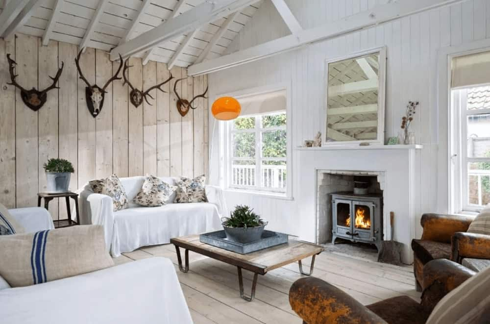 An all wood living room designed with antler decors that are mounted on the beadboard wall. It has comfy seats and a wood plank coffee table facing the fireplace with a white framed mirror on top.
