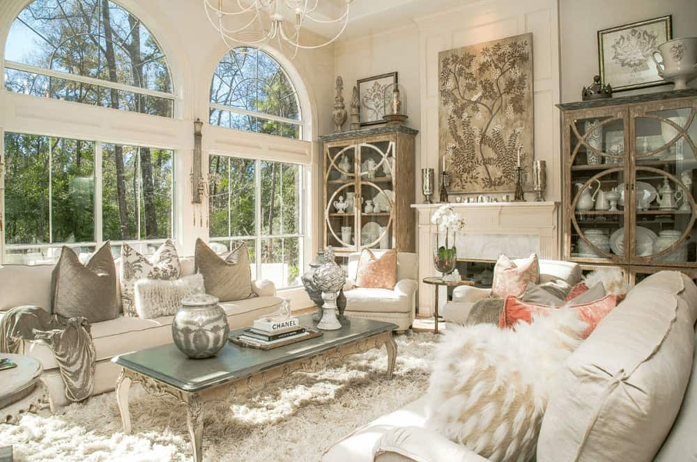 A pair of wooden display cabinets flank a fireplace that's accented with a foliage artwork. It has white seats surrounding a classy coffee table and large arched windows overlooking the enchanting forest.