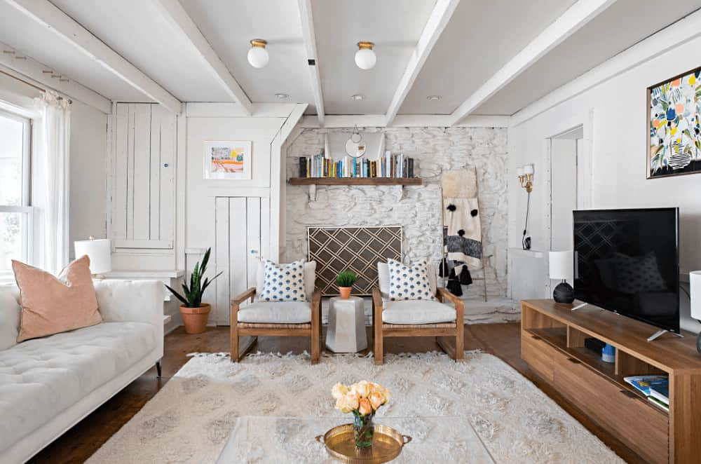 Shabby-chic style living offers cushioned chairs and a tufted sofa that faces the flat-screen TV on a wooden stand blending in with the hardwood flooring. It includes colorful artwork and a wooden floating shelf mounted on the white stone accent wall.