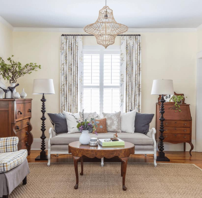 Shabby-chic style living room offers a plaid armchair and gray sofa filled with neutral pillows. It includes wooden cabinets that complement the round coffee table over a jute rug lighted by a wicker pendant.