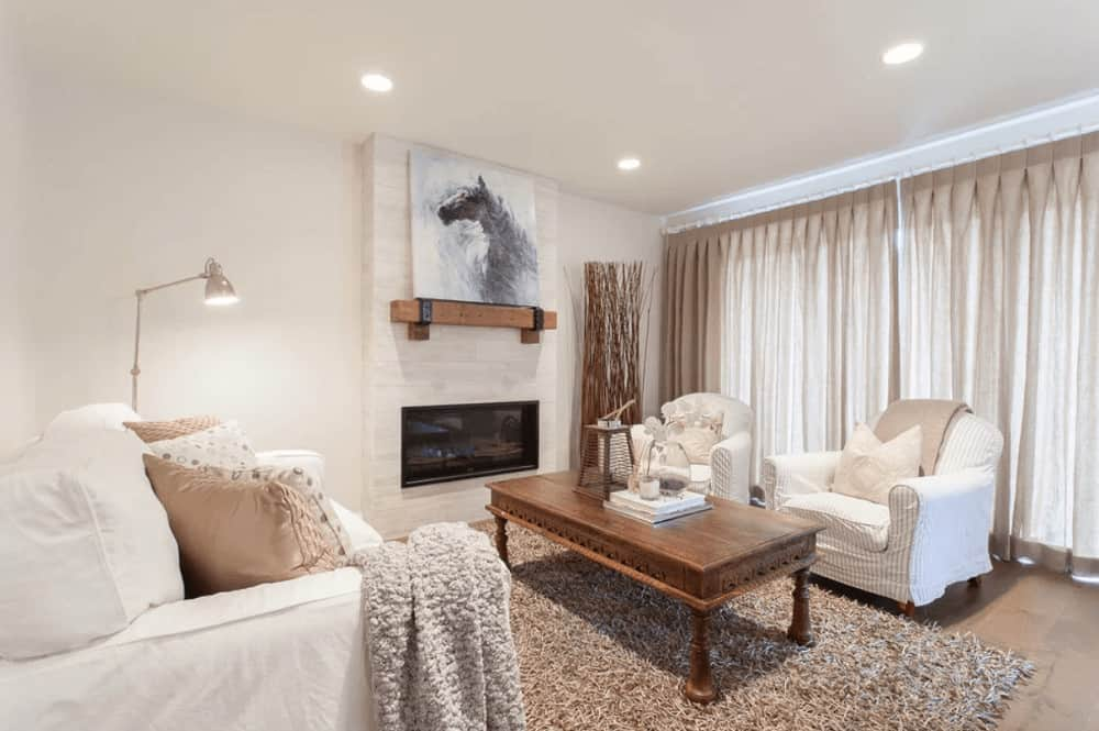 White living room with comfy seats and a wooden coffee table over a shaggy area rug. It includes a fireplace lined with a wooden mantel that's topped with a lovely horse artwork.