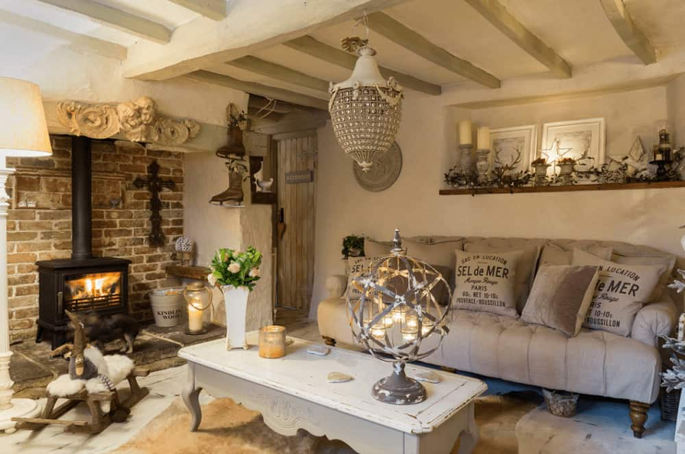 A brick wall sets a striking backdrop to the freestanding fireplace across the distressed coffee table. This room is illuminated by a spherical lamp and a unique chandelier that hung from the beamed ceiling.