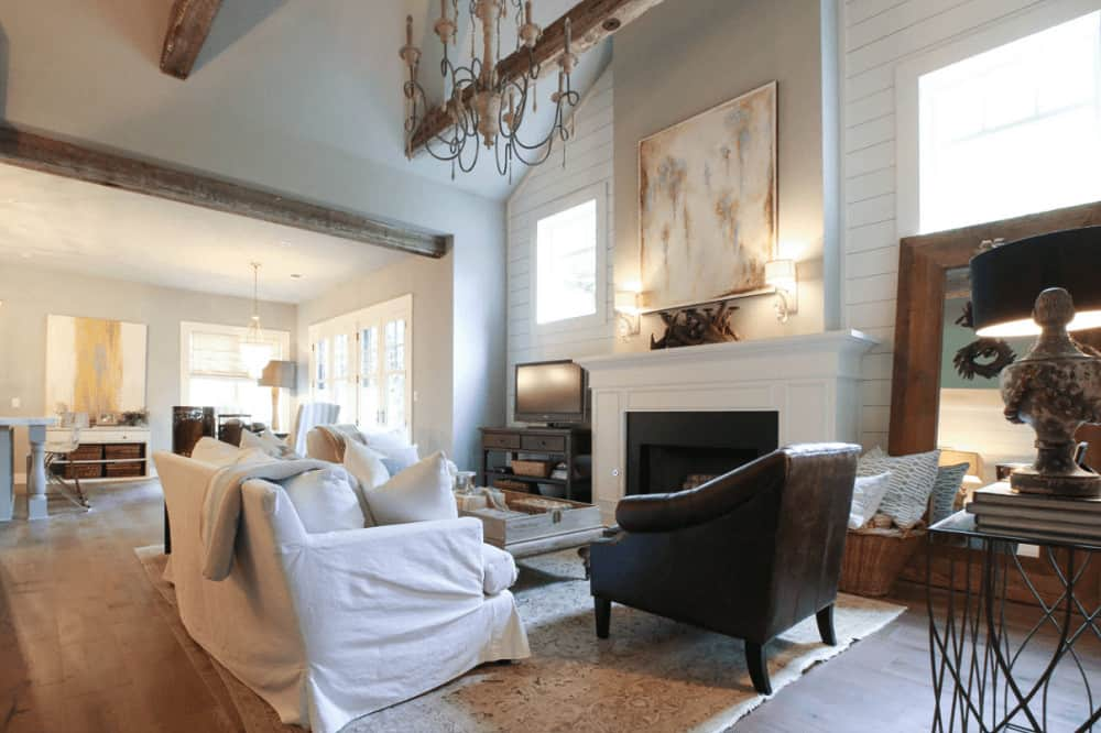 An abstract painting lighted by glass sconces hangs above the fireplace flanked by a large framed mirror and dark wood shelving. It faces the comfy seats and a wooden coffee table over a shabby chic area rug.