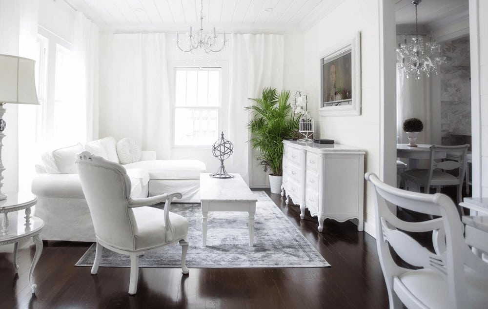 This living room is filled with white furniture that blends in with the walls and shiplap ceiling. It includes a gorgeous chandelier and a distressed area rug that lays on the rich hardwood flooring.