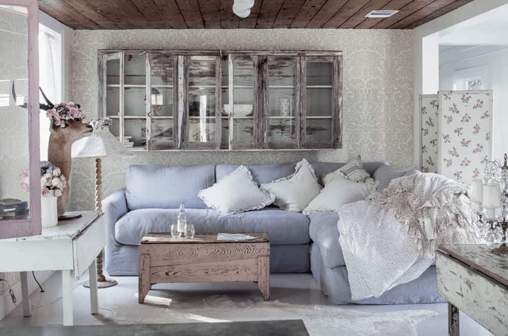 A floating glass front cabinet hangs above the blue L-shaped sofa paired with a wooden coffee table. This room has a rustic wood plank ceiling and tiled flooring topped by a white cowhide rug.