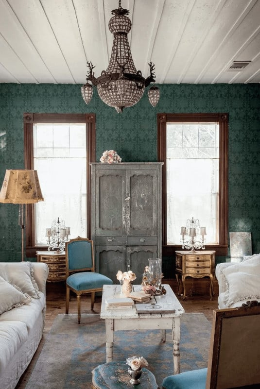 Clad in green patterned wallpaper, this living room showcases a distressed coffee table and cabinet flanked by classy side tables and lamps. It includes cozy seats and a large chandelier that hung from the shiplap ceiling.