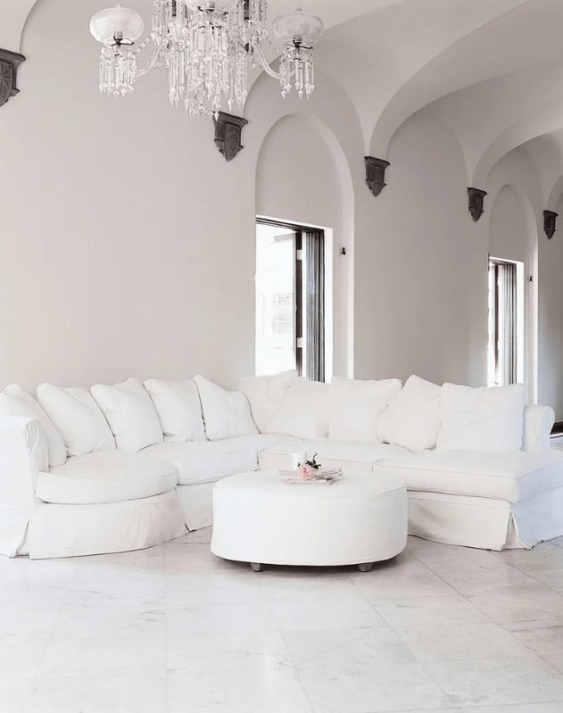 An all-white living room illuminated by a crystal chandelier that hung from the high vaulted ceiling. It has a skirted sectional sofa and a round ottoman that sits on tiled flooring.