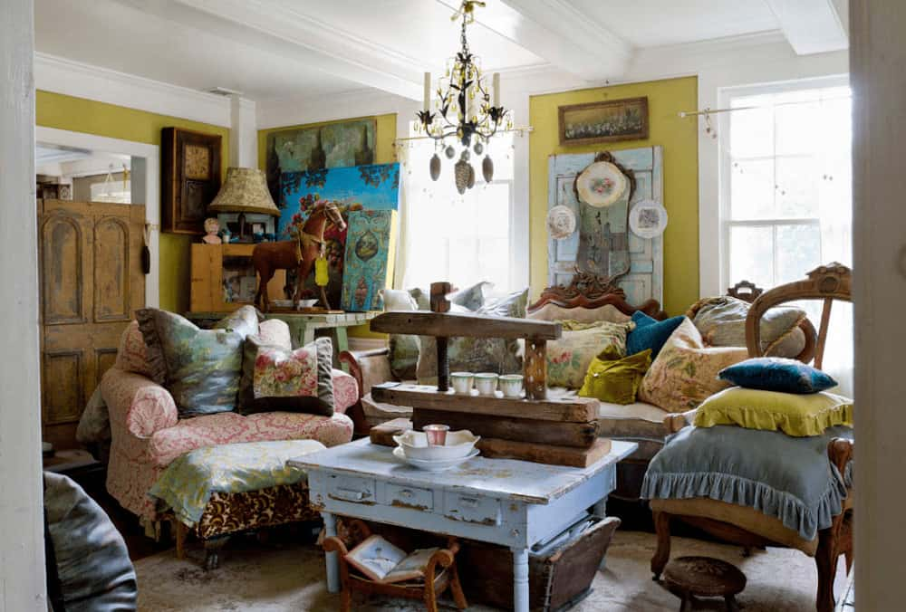 This living room is designed with decorative plates and layered artworks against the yellow wall. It has mismatched seats and a distressed blue coffee table over a vintage area rug.