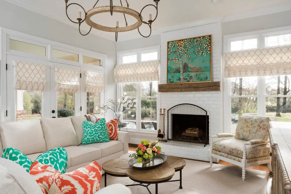 Red and green patterned pillows on a gray sectional bring a pop of color in this living room with an iron coffee table and a floral chair that sits next to the fireplace with a gorgeous tree artwork on top.