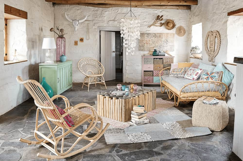 Shabby-chic style living room with white stone walls and flagstone flooring topped by layered rugs. It includes pastel cabinets and wicker chairs paired with a glass top coffee table.