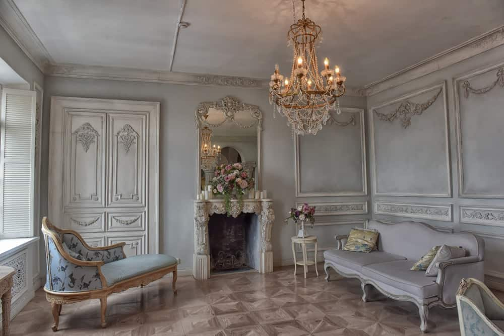 A fancy chandelier illuminates this glam living room offering classy seats and a fireplace with a gorgeous mirror on top designed with intricate details. It has tiled flooring and gray walls clad in ornate wainscoting.