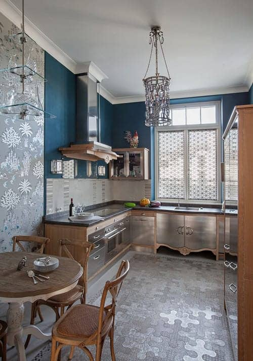 Silver patterned wallpaper complements the puzzle rug along with stainless steel appliances and cabinets. This kitchen showcases a cylindrical chandelier and sleek range hood fixed against the blue wall.