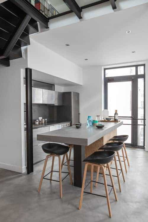 Modern bar stools sit at a breakfast island with a gray countertop. It is accompanied by stainless steel cabinets and a gray fridge that blends in with the backsplash and concrete flooring.