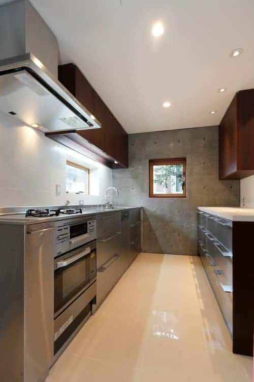 Stainless steel appliances blend in with the silver lower cabinets in this kitchen with white backsplash tiles and dark wood upper cabinets lighted by recessed ceiling lights.
