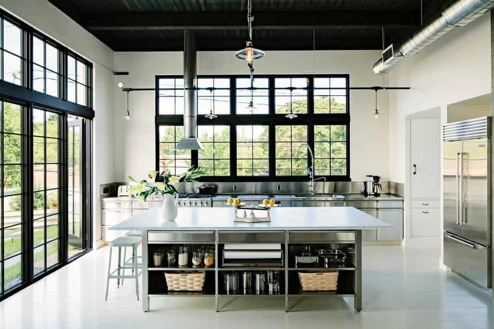 Industrial kitchen with white tiled flooring and aluminum framed windows overlooking the outdoor greenery. It includes stainless steel cabinets and appliances along with a marble top island that's fitted with open shelving.