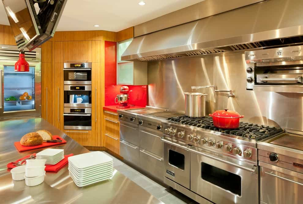 Silver kitchen with subtle orange accents features wooden cabinets and stainless steel appliances matching with the backsplash and countertop. It is illuminated by a dome pendant and recessed ceiling lights.