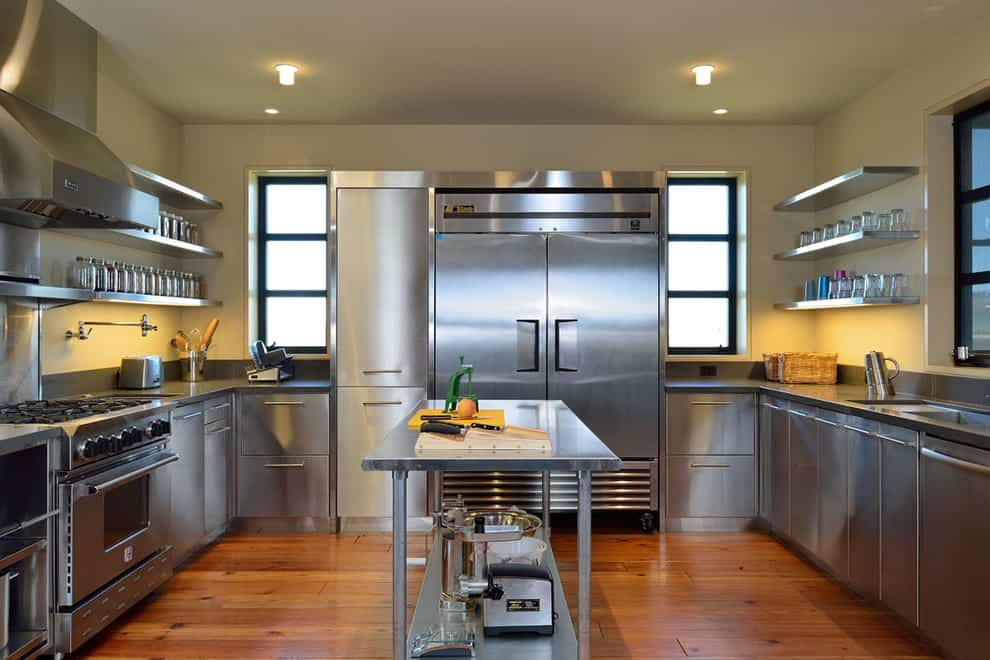 Stainless steel cabinets and appliances surround a matching kitchen island over the rich hardwood flooring. It is accompanied by recessed lights and floating shelves filled with jars and glassware.