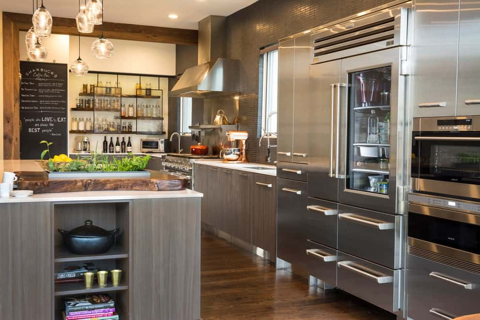 Glass pendant lights illuminate the island bar with a quartz countertop and built-in shelving. It complements the cabinets and appliances against the gray backsplash tiles.