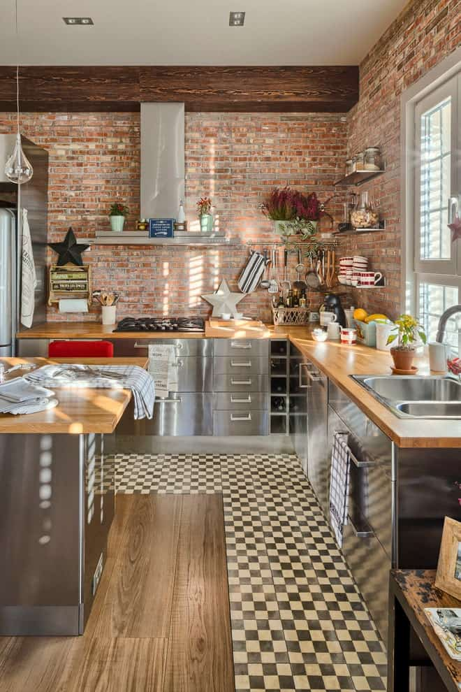 Red brick walls add texture in this kitchen with checkered flooring and regular white ceiling lined with a large wood beam. It includes a dual sink and stainless steel cabinets matching with the kitchen island that's topped with a wooden counter.
