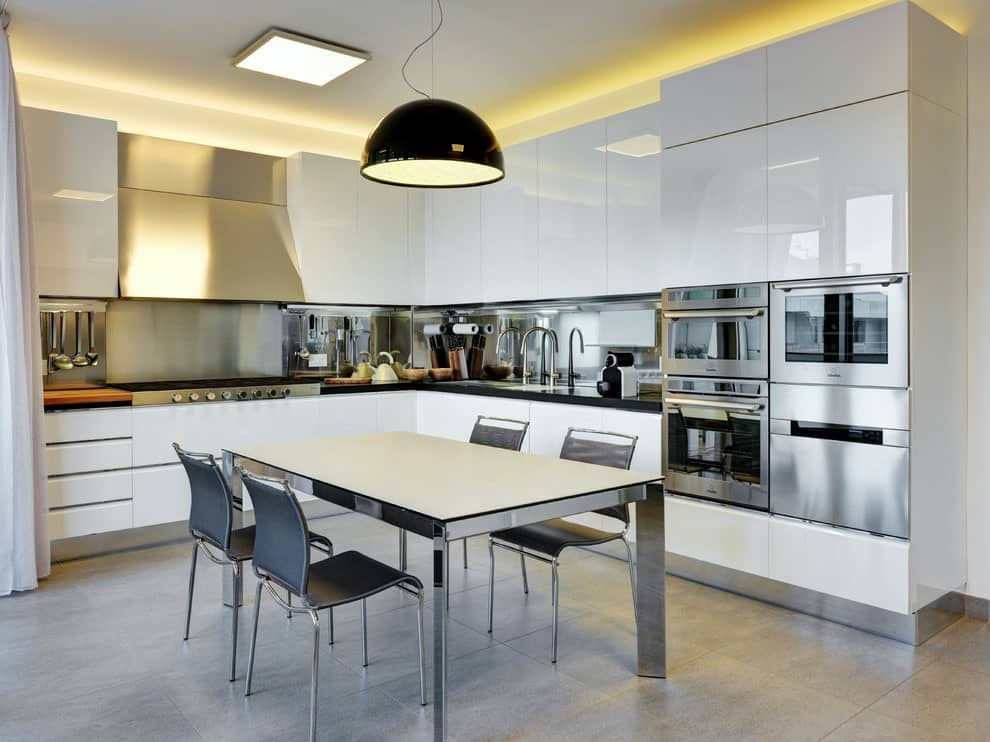 An eat-in kitchen with stainless steel appliances and high gloss cabinetry complementing the dining set that's lighted by a large black dome pendant. It includes black countertops and a sleek vent hood fixed above the metallic backsplash.