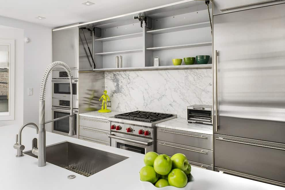 Minimalist kitchen with white marble backsplash and inset appliances concealed with stainless steel cabinets. It includes a quartz top island bar fitted with a sink and chrome fixtures.