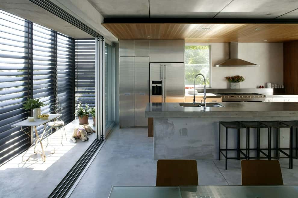 A concrete island bar complements the tiled flooring in this contemporary kitchen with a dual sink and stainless steel appliances matching with the silver cabinets.
