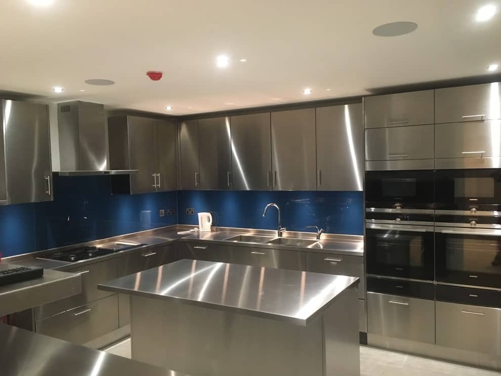 Blue high gloss backsplash stands out against the stainless steel cabinets in this kitchen with a matching island bar and black appliances illuminated by recessed ceiling lights.