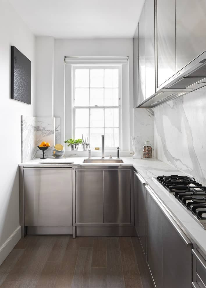 Small kitchen boasts stainless steel cabinets and marble countertops that extend to the backsplash tiles. It has hardwood flooring and white framed windows allowing natural light in.