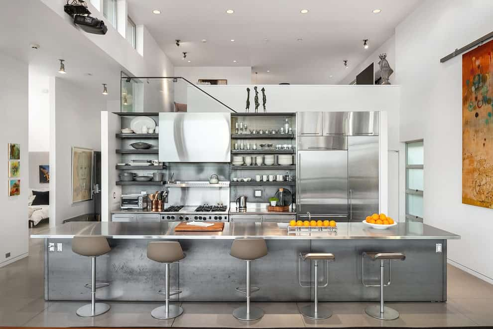 Open concept kitchen offers stainless steel appliances and cabinetry along with floating shelves mounted on the metallic backsplash. It includes an island bar that's lined with gray stools.