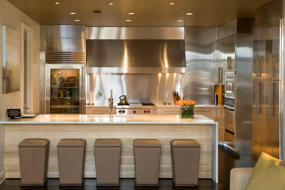 Tall ottomans sit at a light wood shiplap peninsula topped with white marble counter. It faces the stainless steel appliances against a matching backsplash lighted by recessed ceiling lights.