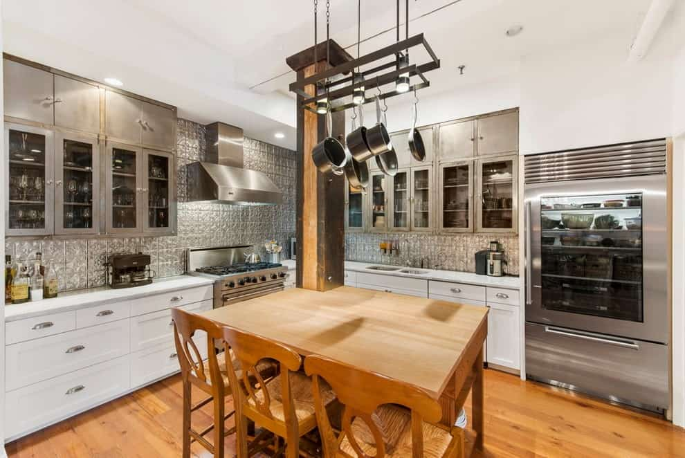 An eat-in kitchen with white lower cabinets and glass front upper cabinets fixed against the metallic textured backsplash. It includes a wooden dining set with a metal pot rack overhead attached to the dark wood column.