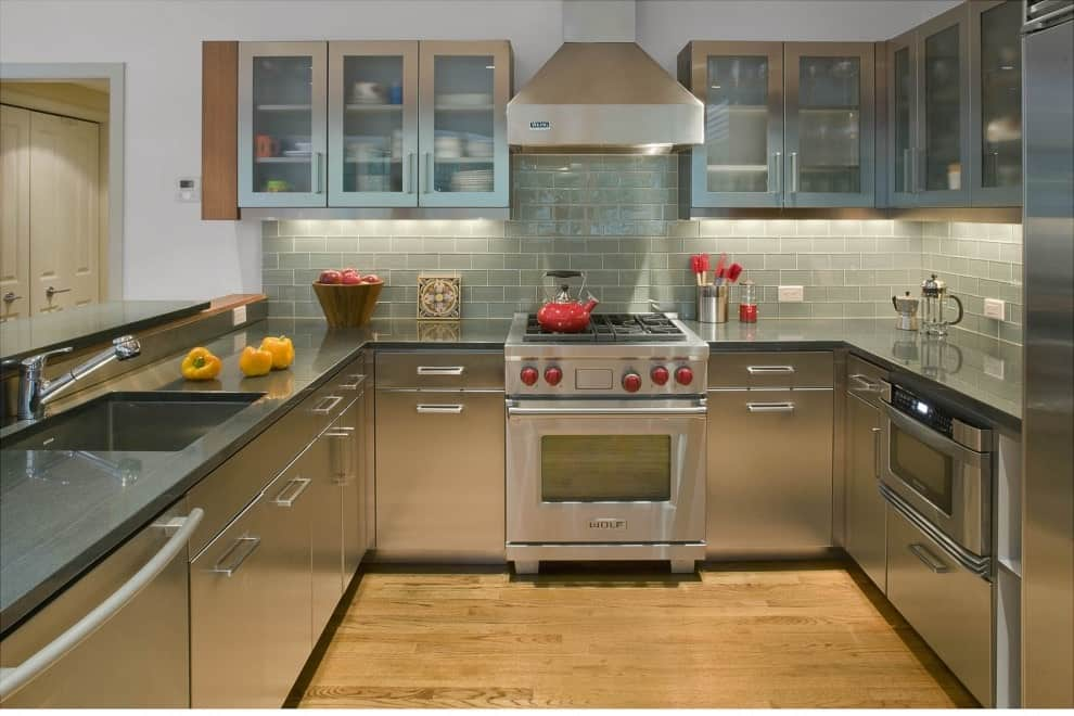 U-shaped kitchen offers glass front upper cabinets and stainless steel lower cabinets that blend in with the appliances. It includes subway tile backsplash and gray countertops fitted with an undermount sink.