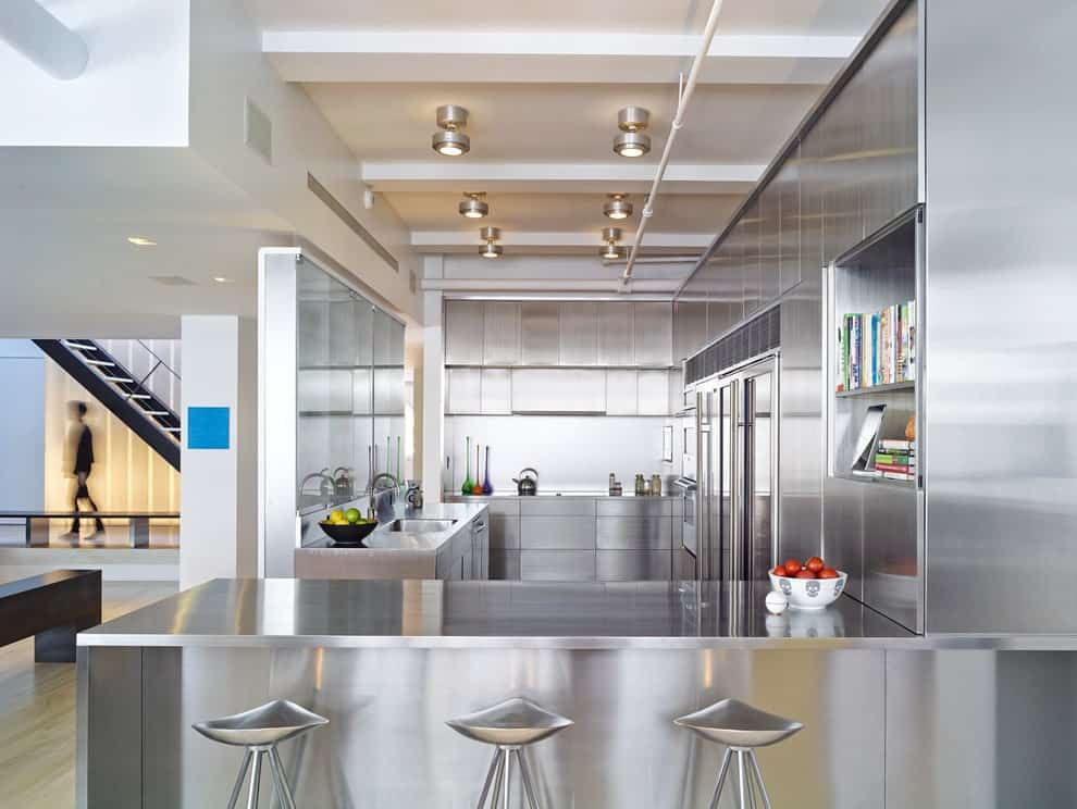 Silver kitchen boasts stainless steel cabinetry and peninsula achieving a cohesive look. It includes chrome bar stools and modern light fixtures mounted on the white beamed ceiling that's lined with exposed pipes.