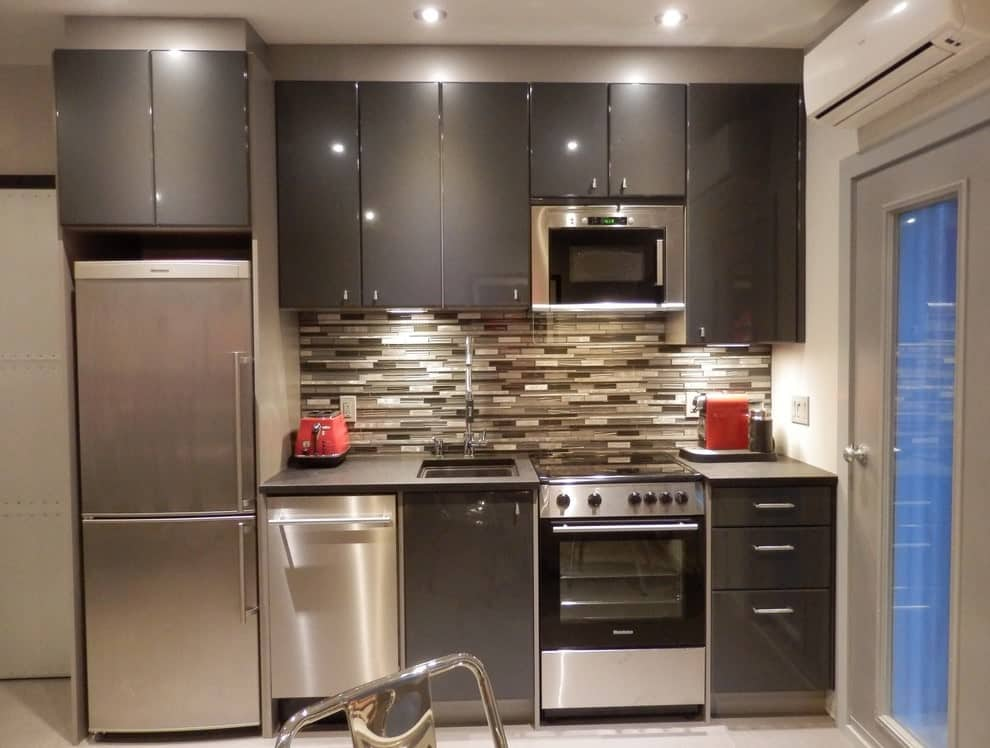 This kitchen features stainless steel appliances and high gloss cabinetry accented with linear mosaic tile backsplash. It has black granite countertops and a single bowl sink paired with chrome fixtures.