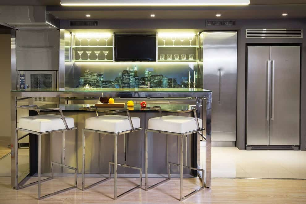 Contemporary kitchen showcases stainless steel appliances and cabinets accented with a stunning mural backsplash. It includes a wall-mount TV and a chrome island bar lined with modern cushioned stools.